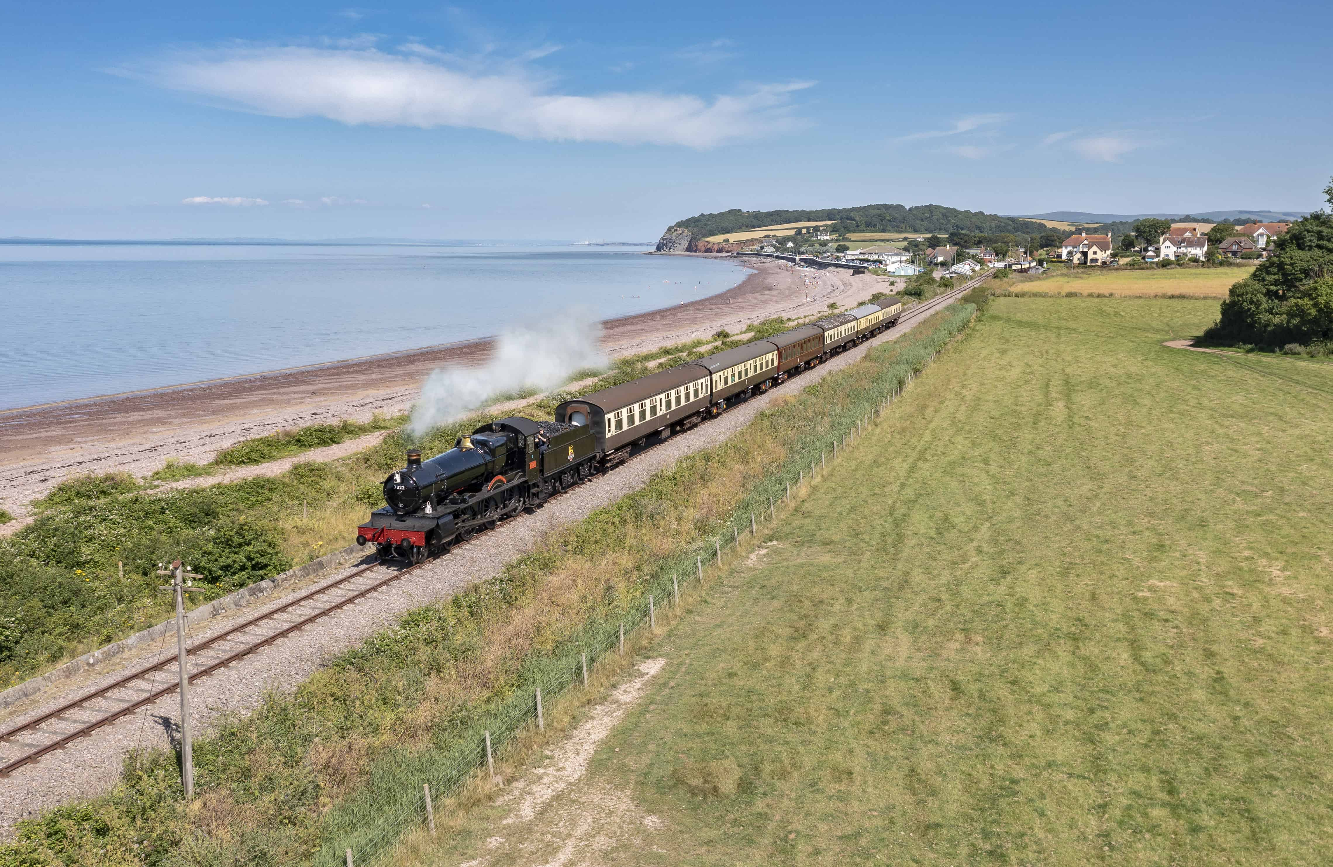 No. 7822 'Foxcote Manor' both leaving Blue Anchor station for Minehead with classic seaside views of the sea and cliffs behind.